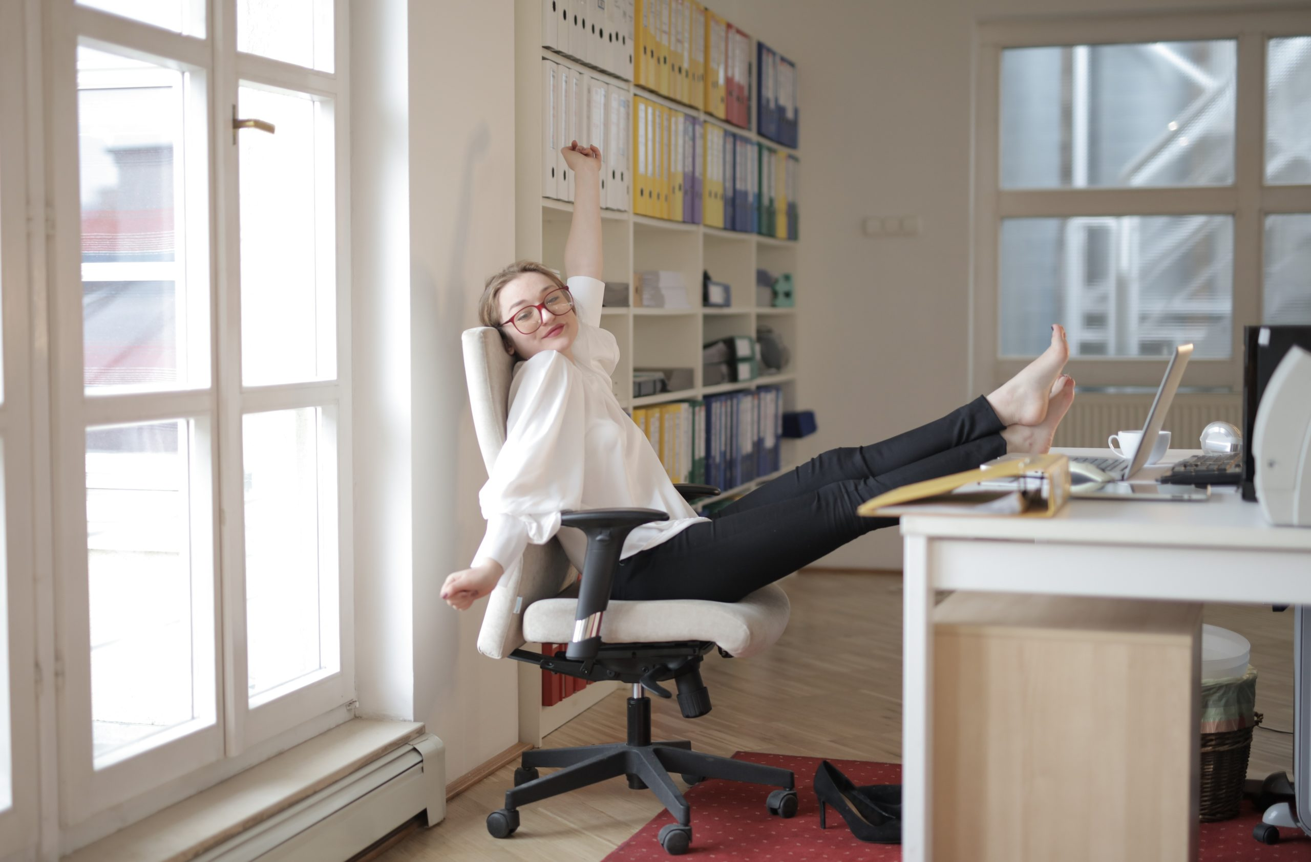 dreamy-female-employee-relaxing-with-feet-on-table-in-office-3791119